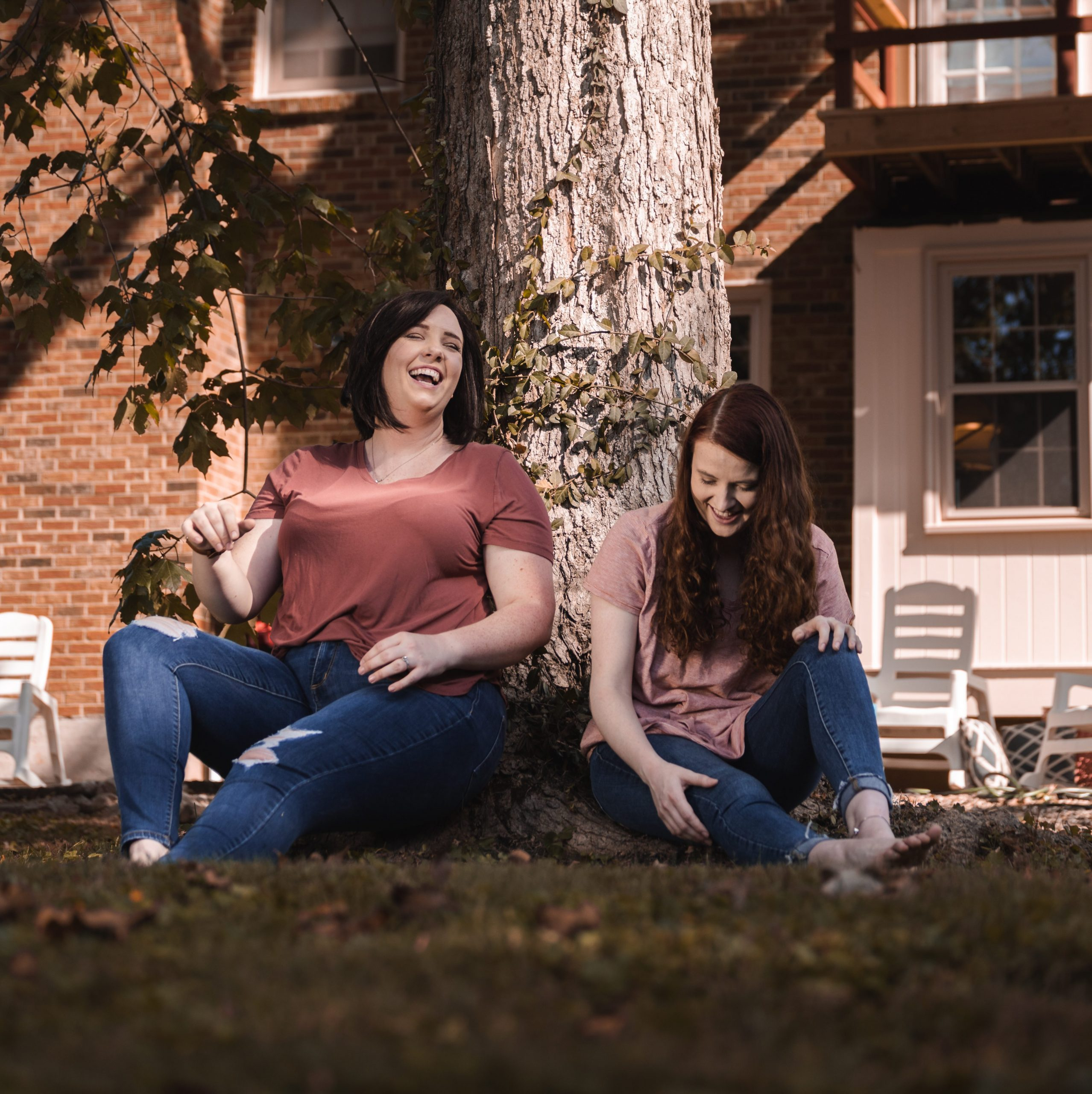 Two women, catherine ballard, and christina wherthey, sitting under a tree on the about crossmore marketing page.